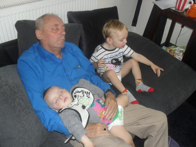 A man dressed in a blue shirt and grey trousers is asleep. In his arms is a little girl fast asleep, next to him is a little boy.