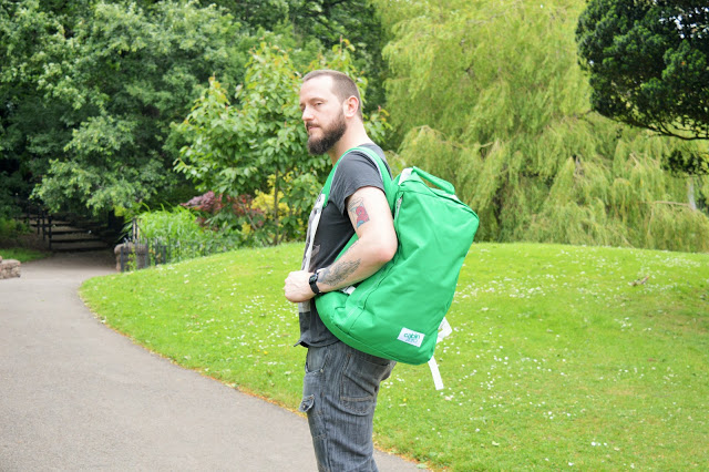 Man with green bag on his shoulder.