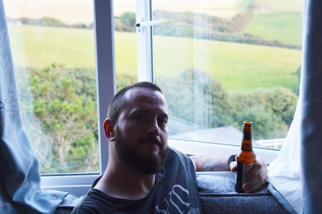 A man drinking a beer on a sofa in a caravan.