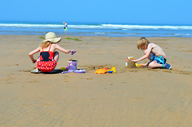 A girl and a boy playing on the beach.