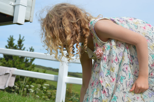 A girl with curly hair reaching down to the grass.