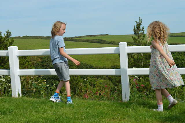 A boy and a girl by a white fence in front of fields.