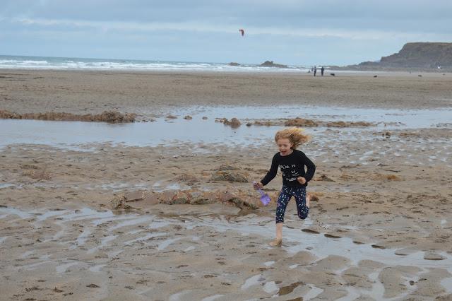 A girl running across the sand.