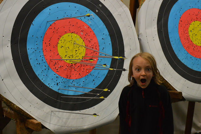 A target with arrows in it and a boy in front looking happy!