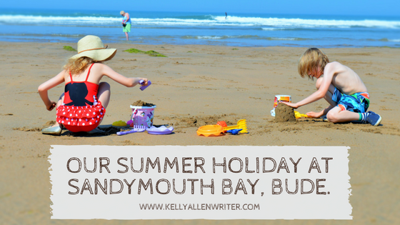 Two children on a beach with title 'Our Summer Holiday at Sandymouth Bay, Bude.'