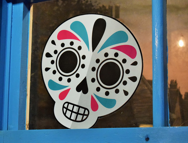 Window with white skull face stuck on it.