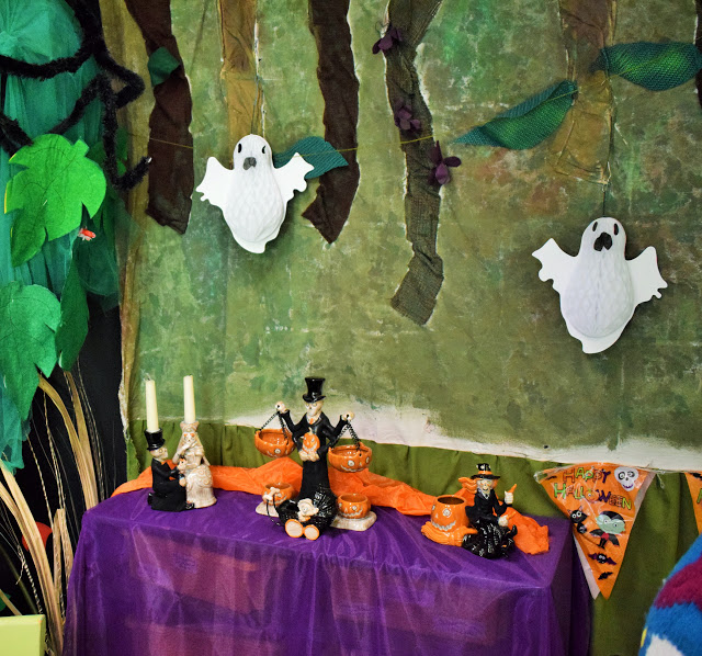Table decorated with Halloween candle holders and skeletons.