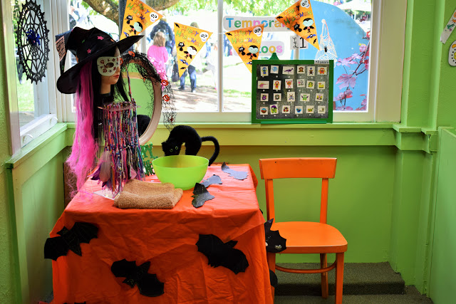Table decorated with black cat, a witch hat and bowl.