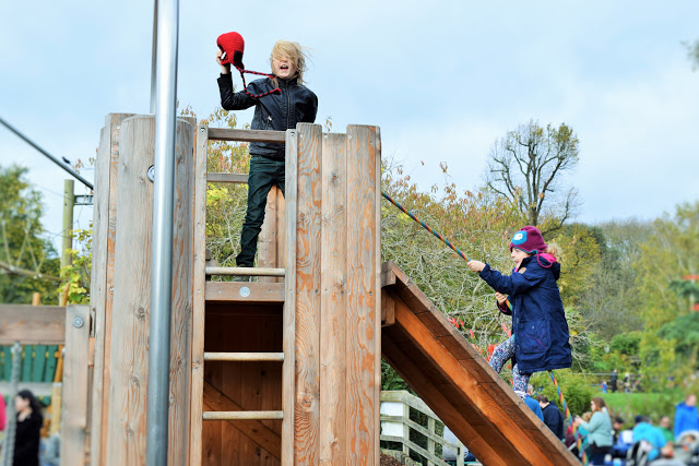 Two children playing on a pirate themed play area.