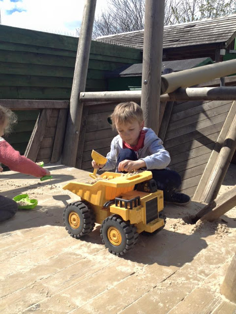George playing with a truck in the sand at Parc Play.