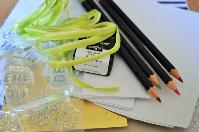 Selection of coloured pencils, stamps, card and ribbon.