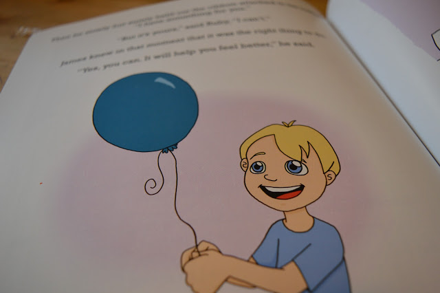 A blonde boy holding a balloon and smiling.