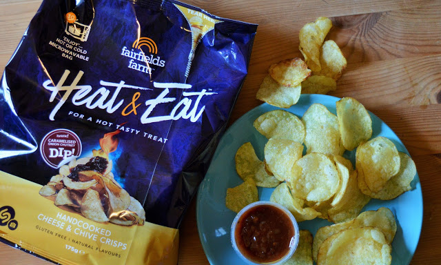 A packet of crisps next to a plate of crisps with a dip on.
