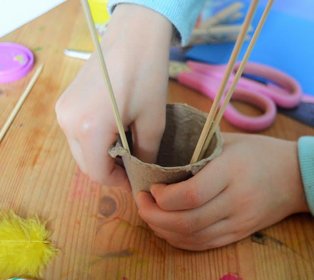 Little hands putting sticks into the pot.