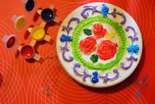 Jewellery lid with painted detail and mini paint pots next to it.