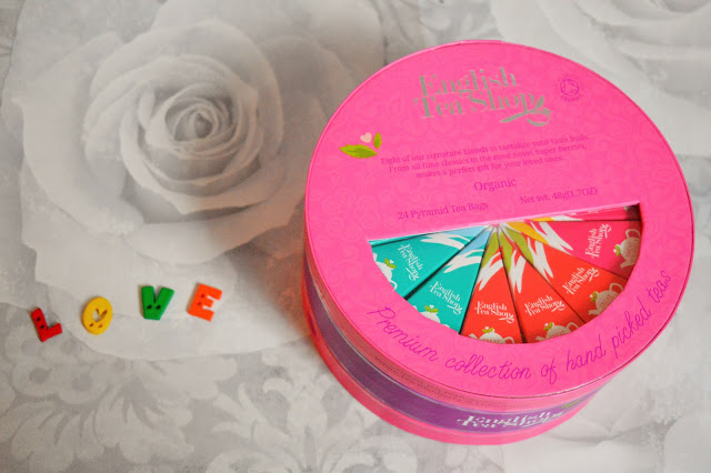 A round pink cardboard box with tea pyramids inside and love spelt out with buttons beside it.