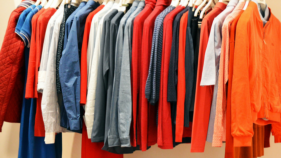 A selection of bright coloured clothes haging along a rail.