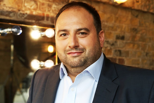 Wynne Evans in a suit smiling.