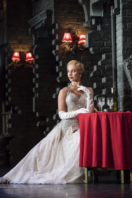 A lady in a long white ballgown sat at a table with drinks.