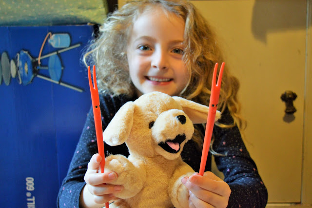 A young girl holding her be my bear and chopsticks!