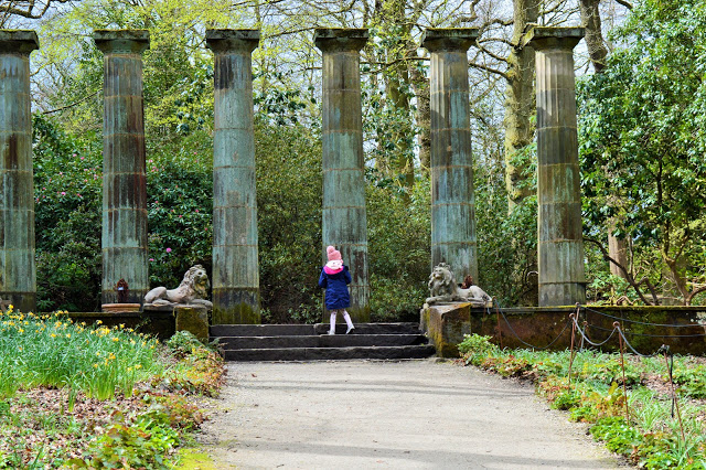6 pillars, two lion statues and a little girl (Molly) walking up some steps,.