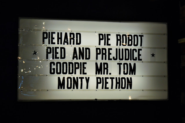 a large screen advertising movies such as 'pie hard' or 'pie robot'